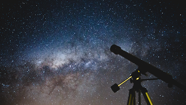 Image of a telescope with a starry night sky behind it