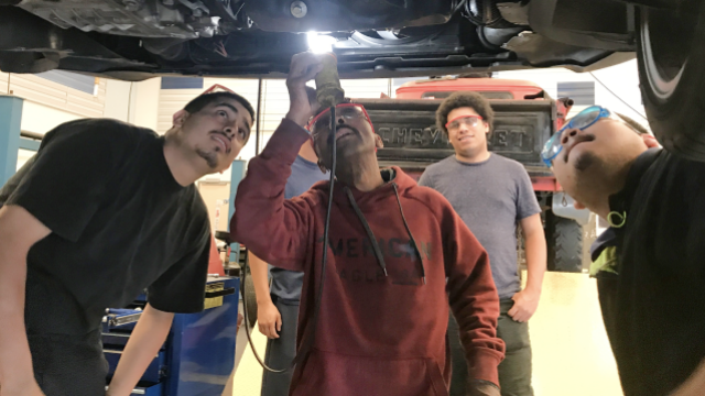 Students working on the undercarriage of a car