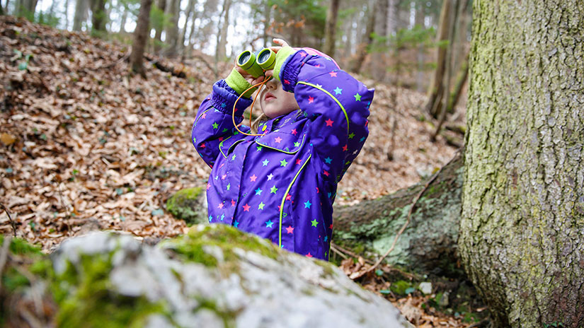 Student in the woods holding binoculars